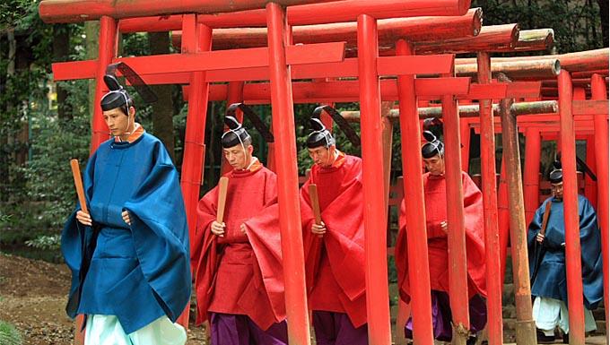 sacerdotes sintoístas pasando a través de un sendero de torii