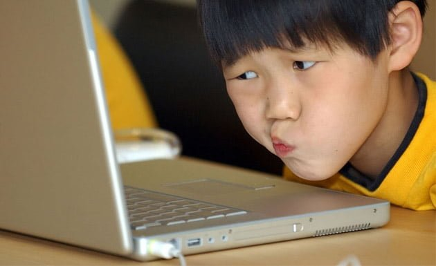 niño asiático en la computadora